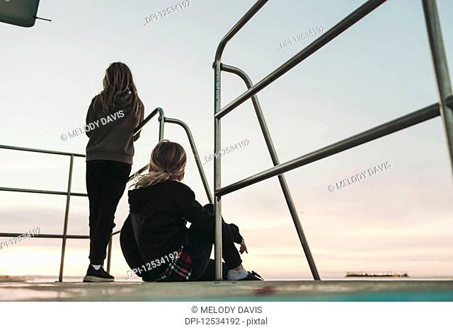 Two girls sit on a lifeguard station at dawn looking out to the ocean; Long Beach, California, United States of America