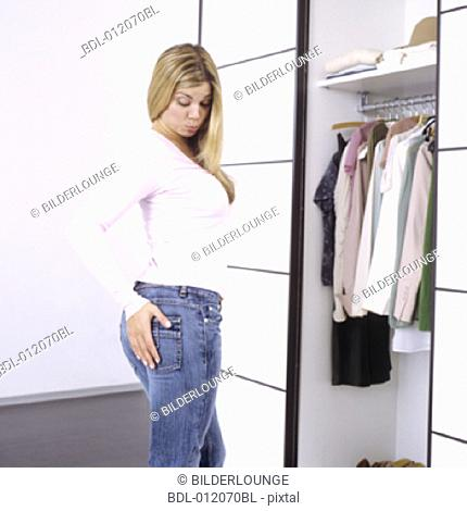 blonde young woman in front of wardrobe seemingly concerned about her figure