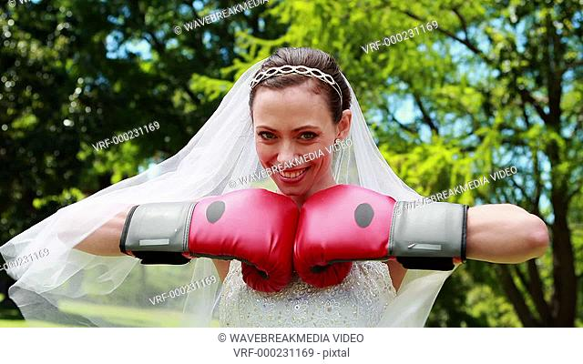 Pretty bride smiling at camera and wearing boxing gloves on her wedding day