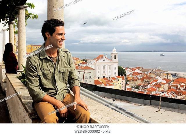 Portugal, Lisboa, Alfama, Miradouro de Santa Luzia, young man enjoying vista