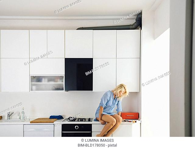 Woman reading on kitchen counter