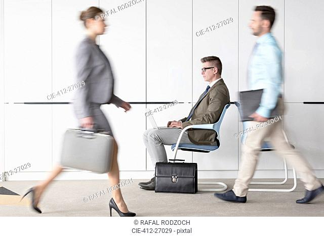 Businessman working at laptop in lobby behind business people on the move