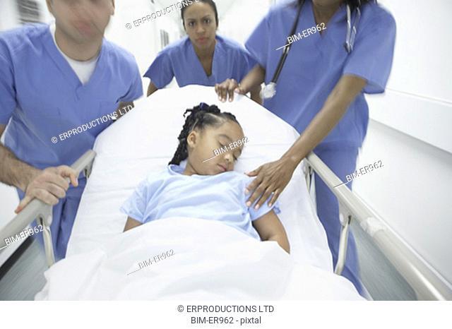 Doctors wheeling African girl in gurney