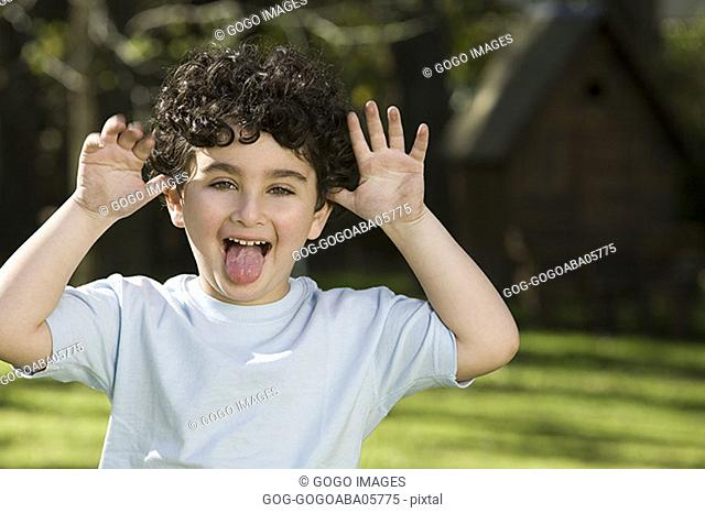 Young boy making a face outdoors