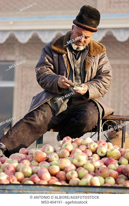 Uighur men sell apples at the Sunday Market. Kashgar (Kashi). Xinjiang Uyghur Autonomous Region. China
