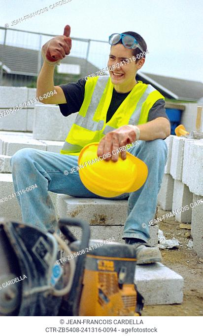 Young builder having a break on site