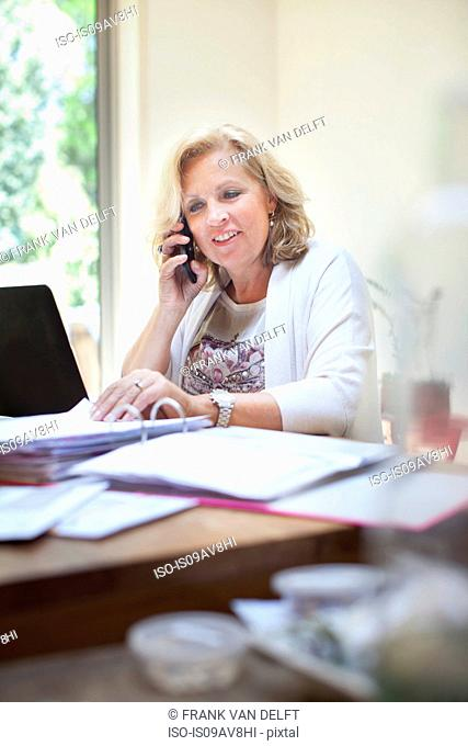 Mature woman sitting at table, looking through paperwork, using smartphone