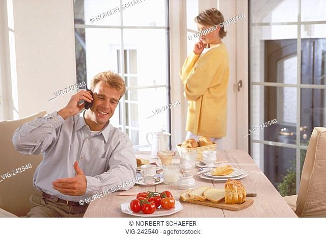 indoor, half-figure, couple mid of 30, man sits at breakfast making a phone call whiles she is standing at the window watching him sceptical  - GERMANY