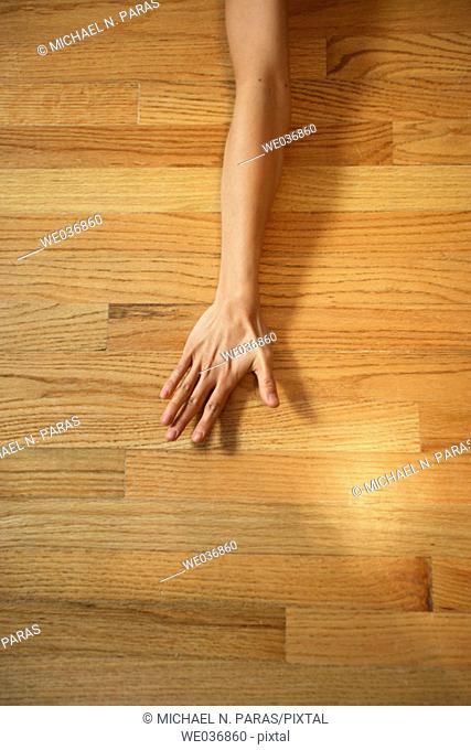 Woman's arm & hand on wood floor