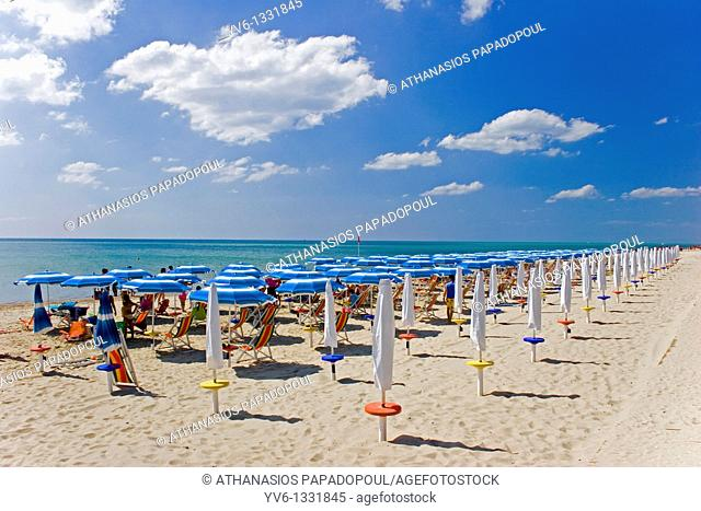 South Italy Puglia Metaponto Coloured umbrella's and deck-chairs in formation by the sea