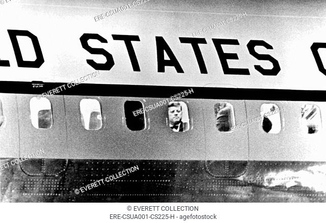 President John Kennedy peers out from window of Air Force One. He was leaving for Paris to meet with French President de Gaulle and then with Soviet Premier...