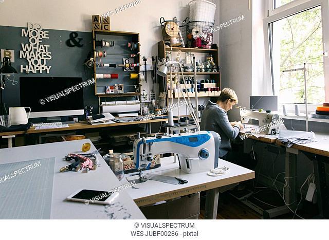 Woman using sewing machine in studio