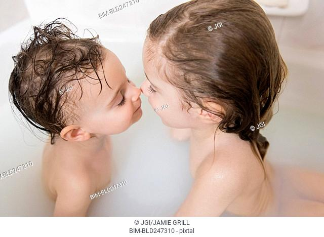 Caucasian boy and girl rubbing noses in bathtub