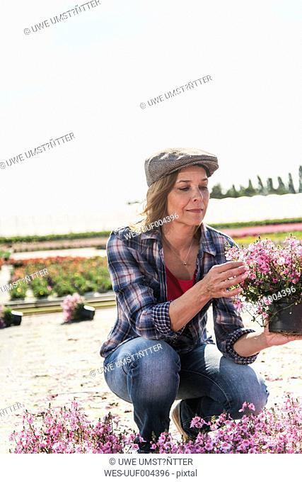 Woman in nursery looking at flower
