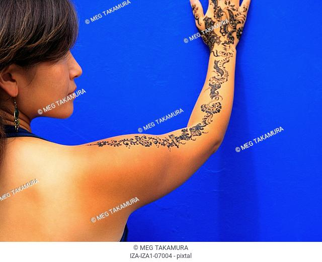 Rear view of a mid adult woman with henna tattoo on her hand