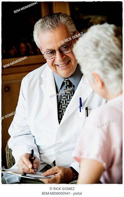 Doctor talking to older patient in home
