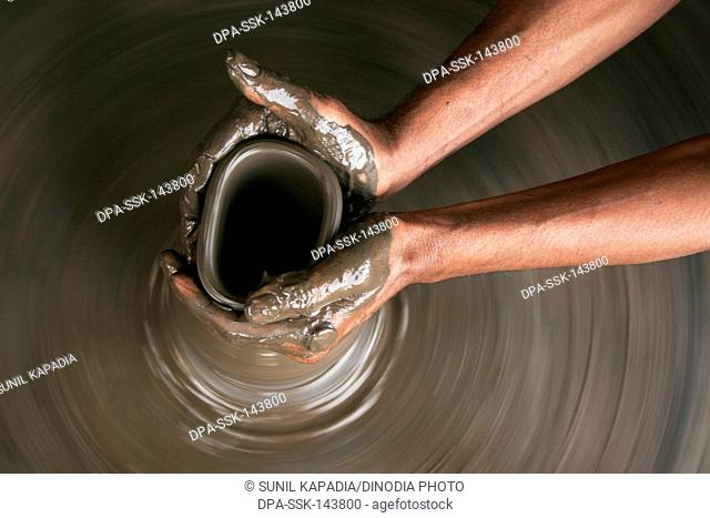 A potter moulding a clay pot on the potter's wheel ; Pune ; Maharashtra ; India