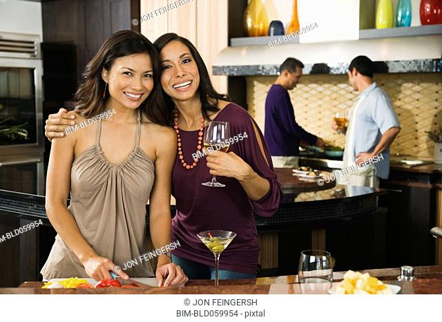 Multi-ethnic women hugging at party