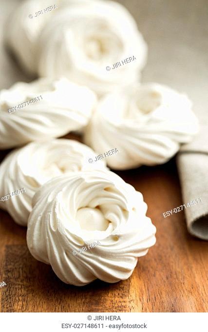 Sweet white meringue on wooden table