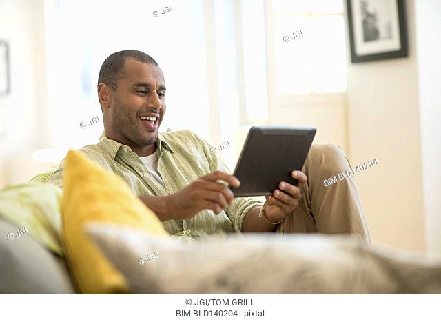 Mixed race man using digital tablet in living room
