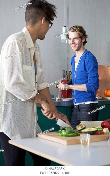 Smiling man preparing food with female friend in kitchen