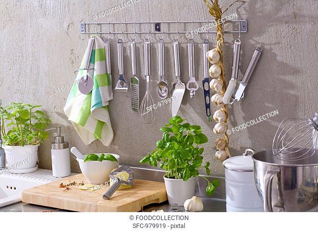 Kitchen utensils, string of garlic, basil, Parmesan etc