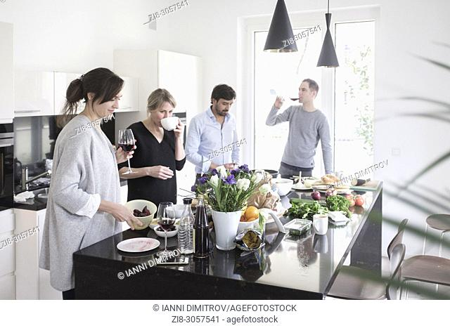 Group of friends preparing food together. Casually chatting , snacking , laughing and enjoying themselves in modern kitchen