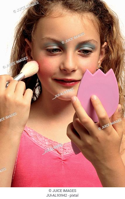 Young girl putting on makeup