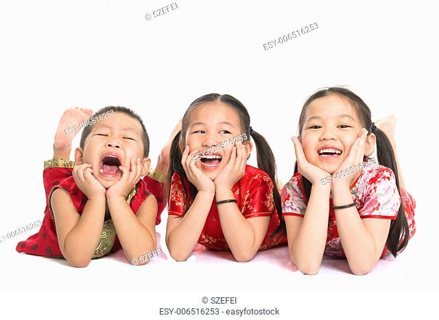 Group of happy young Asian children in traditional Cheongsam dress lying on floor with head on hands, isolated on white background
