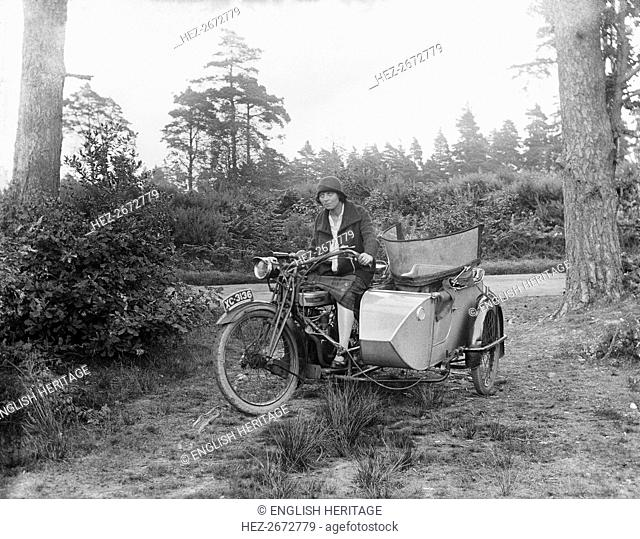 A woman riding a Douglas flat-twin motorcycle with a sidecar, 1900-1910. Artist: Unknown