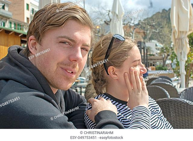 Young handsome happy couple sit close in cafe and squint in stark sunshine on a sunny spring day in Mallorca, Spain