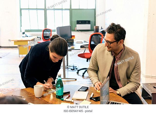 Colleagues in office at table writing
