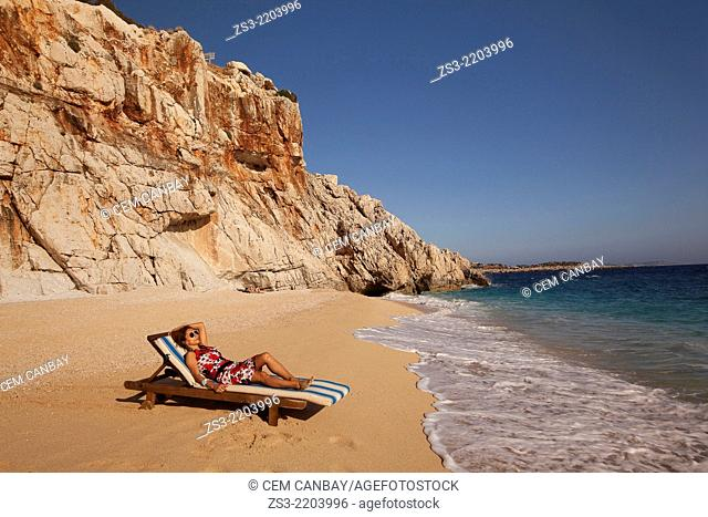 Woman lying on sunbed at Kaputas beach, between Kalkan and Kas, Antalya Region, Turkish Riviera, Turkey, Europe