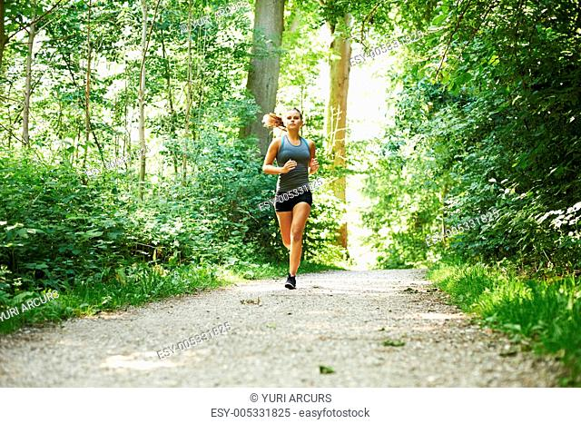 A young woman running in a beautiful forest