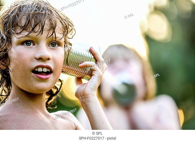Boys playing with tin can phone