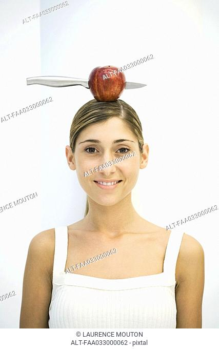 Young woman balancing apple with a knife stuck in it on head, portrait