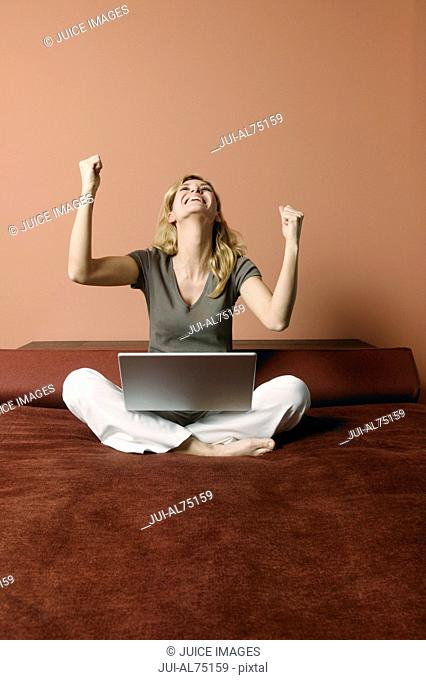 Portrait of a young woman celebrating her success on a laptop