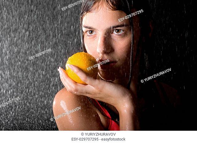 portrait of pretty teen with orange in water studio