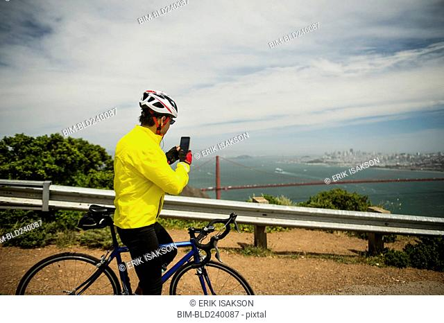 Hispanic man on bicycle photographing waterfront with cell phone