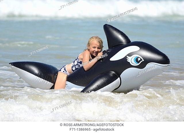 Six year old girl at the beach playing in the surf on inflatable Orca Mimiwhangata Northland, New Zealand