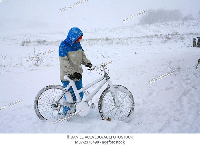 girl picking up bicycle in a snowy day. Spain
