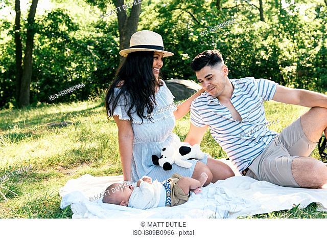 Parents gazing at baby son on picnic blanket in Pelham Bay Park, Bronx, New York, USA