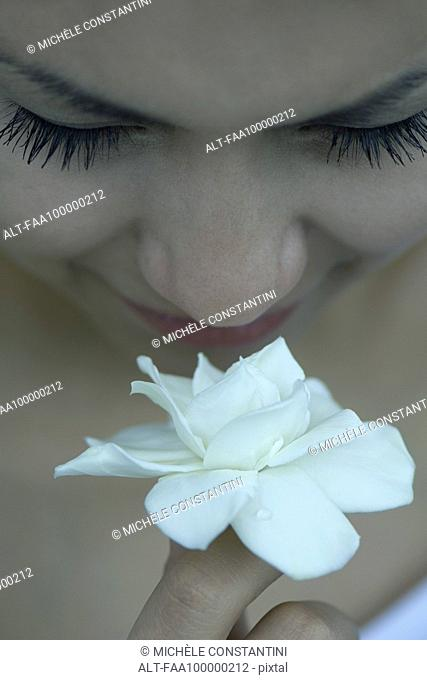 Young woman smelling gardenia, close-up