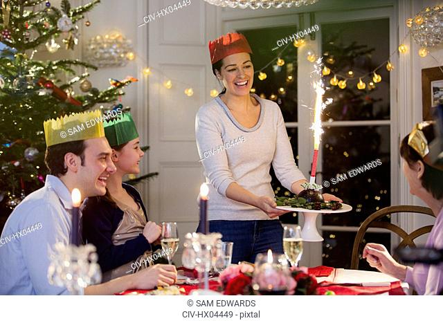 Smiling woman in paper crown serving Christmas pudding with fireworks to family at dinner table