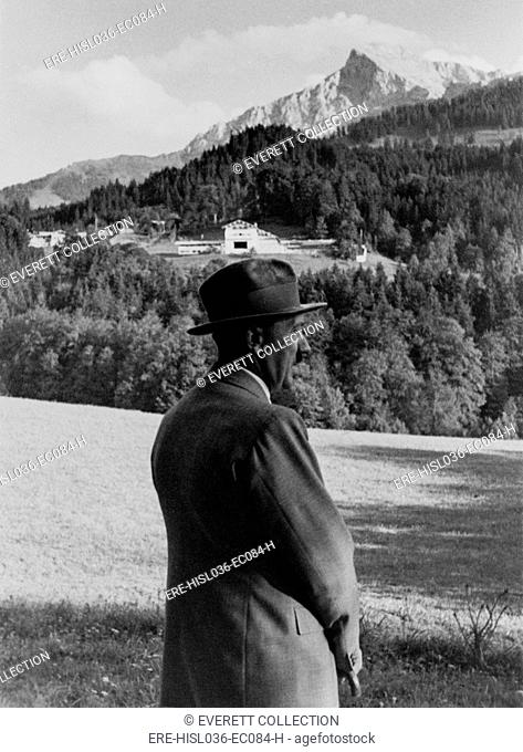 Adolf Hitler looking over his estate, in Berchtesgaden, German. His country house under construction, on the Obersalzberg in the background. Ca. 1935