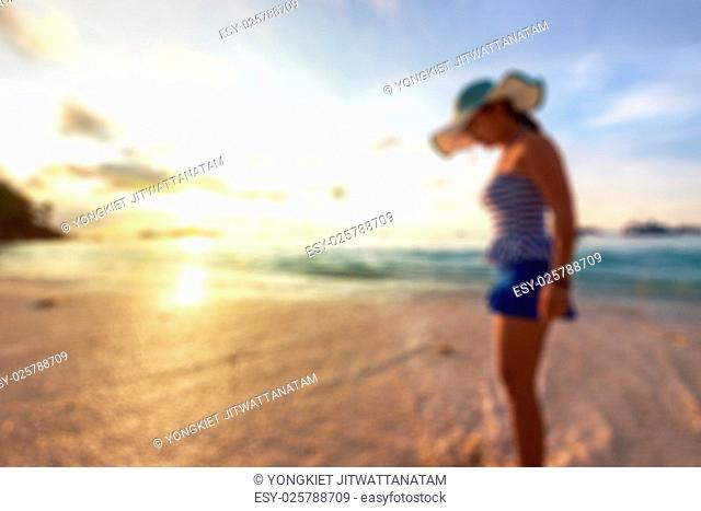 Blurred image for background, Tourist woman in a swimsuit watching sunrise on the beach and sea at Miang island in Mu Koh Similan National Park
