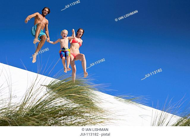Exuberant family jumping over sand dune beach hill