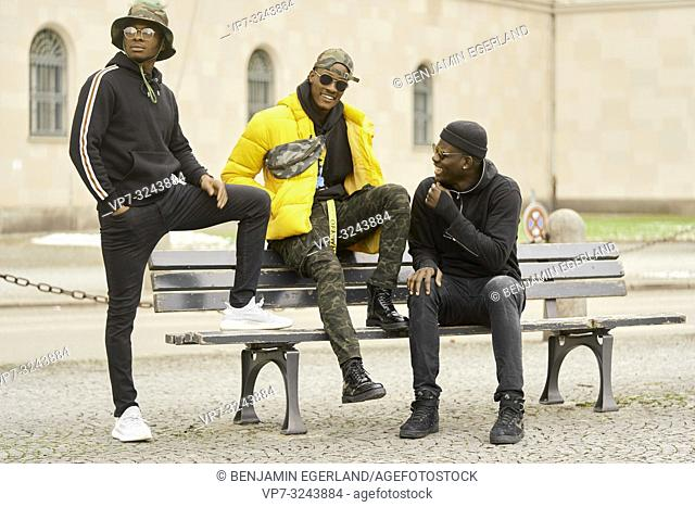 three urban male friends on bench at street in city, in Munich, Germany