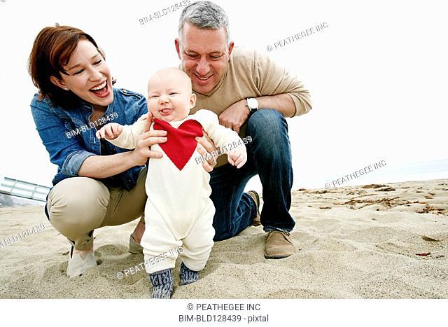 Parents helping baby walk on beach