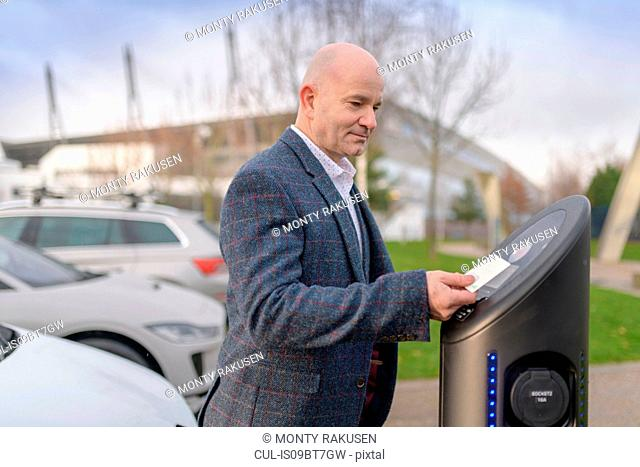 Businessman using access card at electric car charging point, Manchester, UK